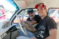 A young Nathan sits behind the wheel of his EH Holden, at the Worongarry Muscle Car Expo. Rod looks on proudly. Photo courtesy of The Gold Coast Bulletin 2009
